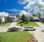 Boat In A Suburban Neighborhood. Suburban Neighborhood - a street in the suburbs with a boat and trailer hitched to a 4 wheel drive truck in summer Royalty Free Stock Photo
