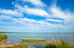 Boat on summer lake bank. Old wooden fishing boat on summer lake bank (Svityaz, Ukraine Royalty Free Stock Photography