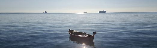 Boat in a sunny day. A picture of a boat in a sunny sea and ships in the background,in a summer day in a greek town,thessaloniki Royalty Free Stock Photo