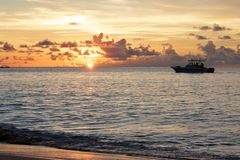 Boat at sunset 1. Fishing boat going towards a romantic and colorful sunset over the Indian Ocean shores of Beau Vallon bay, Mahe island, Seychelles Stock Images
