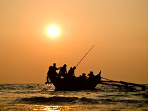 Boat in sunset. Silhouette of fishers boat in sunset on the sea Royalty Free Stock Image
