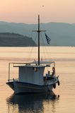Boat at sunset. A boat anchored on the riverside at sunset Stock Image