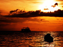 Boat sunset. Over calm water royalty free stock image