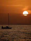 Boat in sunset. One alone little wooden sailing boat in the beautiful sunset on the Adriatic sea (Croatia-Dalmatia). Vertical color photo royalty free stock photography