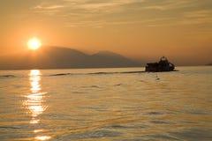 Boat at sunset. A boat sailing away at sundown, Lago d'Iseo, Italy stock image