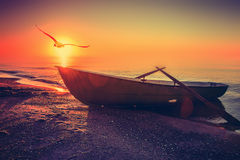 Boat sunset. Fishing boat on a coast near ocean at sunset time stock image