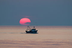 boat in sunset on the horizon above sea Stock Photos