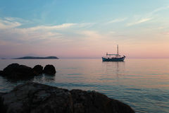 Boat on the sunset. Old wooden little boat wait for the sunset in Greece Royalty Free Stock Photography