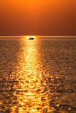 Boat in the sunset in the sea with reflections and clouds. Boat in the sunset in the sea with reflections and orange clouds Royalty Free Stock Images