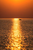 Boat in the sunset in the sea with reflections and clouds Royalty Free Stock Image