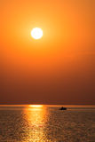 Boat in the sunset in the sea with reflections and clouds Royalty Free Stock Images