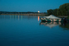 Boat at sunset. On the shore of a large reservoir Stock Photo