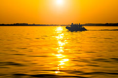 Boat at sunset. Silhouette of a boat floating in the sunset Stock Image