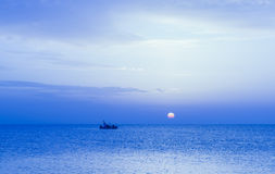 Boat at sunset. A small fishing boat in a boundless sea advances slowly in the light of a pale sun Stock Photo