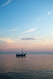 Boat on the sunset vertical. Old wooden little boat wait for the sunset in Greece with dynamic clouds Stock Image