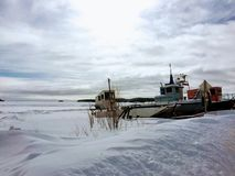 Boat surrounded by vast ocean of snow in Fort Chipewyan during t. He winter months royalty free stock photos