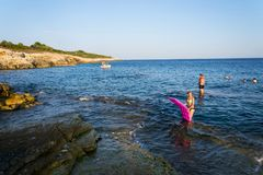 Boat with swimming people on Kamenjak peninsula by the Adriatic Sea in Premantura, Croatia. PREMANTURA, CROATIA - JULY 26: Boat with swimming people on Kamenjak stock photo