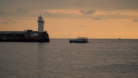 The boat swims past the pier with a lighthouse. evening time stock video footage