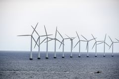 The boat swims by the wind power stations Stock Images
