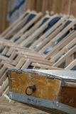 The boat tail of a wooden rowing boat and in the background a series of suspended empty deckchairs lined up in order on the beach stock photo