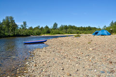 Boat and tent on the Bank of the river. Royalty Free Stock Photos