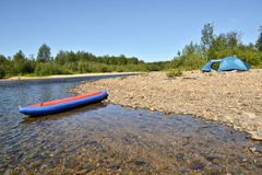 Boat and tent on the Bank of the river. Royalty Free Stock Photography