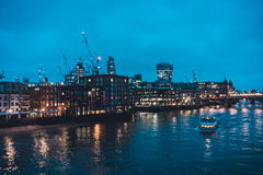 Boat on Thames River and London Skyline at Night Stock Images