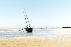 Boat and tidal shore. Fishing boat waiting on tidal shore stock photo