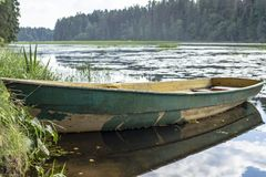 Boat is tied on the bank of the river, against the backdrop of the forest, in the countryside on a summer day. Rustic scenic. Boat is tied on the bank of the royalty free stock photography