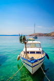 A boat tied on a dock on the crystal clear blue sea Stock Photo