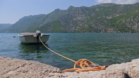 A boat tied to the shore. A boat tied with an orange rope to the shore rocks on the waves stock footage