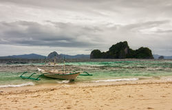 Boat tied to shore at stormy weather under heavy clouds. With waving sea, El Nido, Palavan, Philippines Royalty Free Stock Photo
