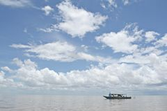 Boat on Tonle Sap lake. Boat sailing on Tonle Sap lake under blue sky and cloudscape, Siem Reap, Cambodia Stock Image