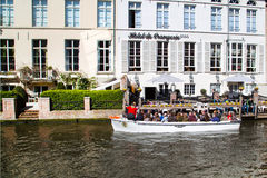Boat tour station with tourists at canal in Bruges, Belgium Royalty Free Stock Images