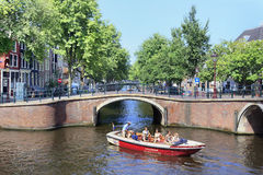 Boat with tourists in a canal, Amsterdam Old Town. Stock Photo