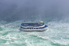 The boat with tourists eager to see the nature miracle in front. Of Niagara Bridal Veil Falls Stock Photography