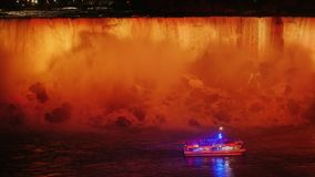 A boat with tourists is floating at the foot of Niagara Falls. Evening, the waterfall is refreshed by floodlights. 4k video stock footage