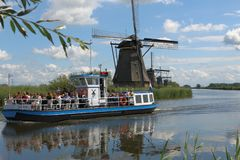 Boat with tourists kinderdijk the netherlands. A boat full of tourists sails slowly next to the windmills in kinderdijk the Netherlands. Een boot vol toeristen stock photos