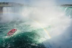 Boat with tourists sailing under the rainbow towards Niagara fal. Ls Royalty Free Stock Photography