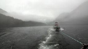 Boat tow in fog on water of Pacific Ocean on background mountains Alaska. stock footage