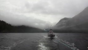 Boat tow in fog on water of Pacific Ocean on background mountains Alaska. stock video