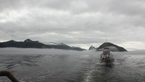 Boat tow in fog on water of Pacific Ocean on background mountains Alaska. Boat tow in fog on water of Pacific Ocean on background mountains in Alaska. Amazing stock video footage