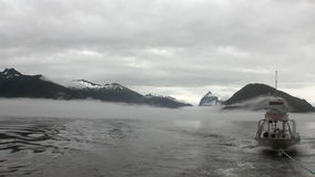 Boat tow in fog on water of Pacific Ocean on background mountains in Alaska. stock video