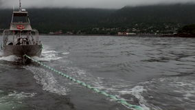 Boat tow in fog on water of Pacific Ocean on background mountains Alaska. Beautiful rest and tourism in a cool climate. Unique picture of nature in America stock footage