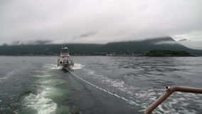 Boat tow in fog on water of Pacific Ocean on background mountains Alaska. Beautiful rest and tourism in a cool climate. Unique picture of nature in America stock video footage