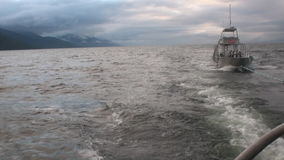Boat tow on water of Pacific Ocean on background mountains in Alaska. stock video
