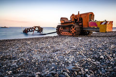 Boat tractor. An old rusty tractor user for bringing in and out of the sea small boats. Shot during sunset time royalty free stock photos