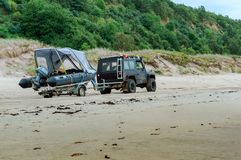 Boat on trailer at the car, jeep with trailer and boat on the beach stock images