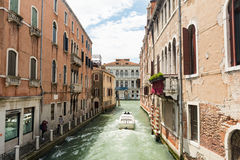 A boat traveling along a canal of Venice while two tourists taking a souvenir photos. VENICE, ITALY - JUNE 4, 2016 - A boat traveling along a canal of Venice royalty free stock image