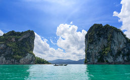Boat traveling pass canyon mountains on a great lake in Thailand Royalty Free Stock Photos
